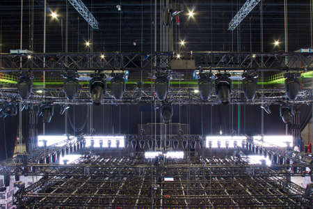 Installation of professional sound, light, video and stage equipment for a tv show. Stage lighting equipment is clamped on a steel trusses for lifting. Chain hoists. Moving head spotlight devices.