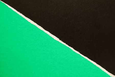 Green and black torn sheet of cardboard paper with diagonal border texture background. Can be used for text.