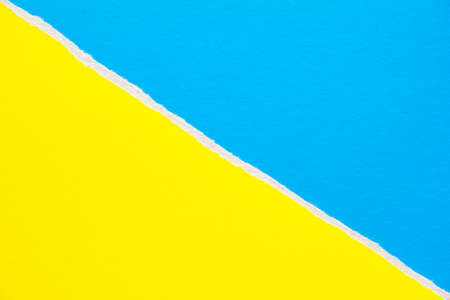 Yellow and blue torn sheet of cardboard paper with diagonal border texture background. Can be used for text.