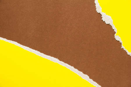 Yellow torn sheet of cardboard on brown paper texture background. Can be used for text.