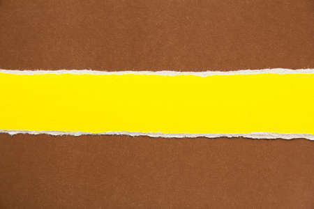 Closeup torn stripe of yellow cardboard on brown paper texture background. Can be used for text.