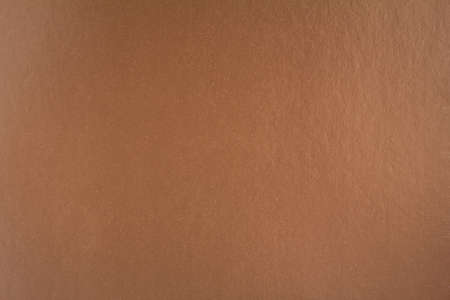 Brown sheet of cardboard paper with gloss surface texture background.