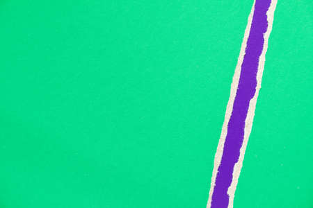 Green torn sheet of cardboard paper with purple violet stripe texture background.