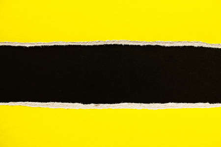 Black and yellow torn and ripped sheet of cardboard paper texture background. Can be used for text.