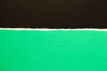 Black and green torn sheet of cardboard paper texture background. Can be used for text.