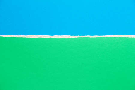 Green and blue torn sheet of cardboard paper texture background. Can be used for text.