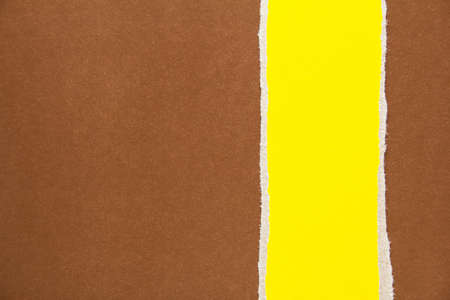 Yellow torn piece of cardboard on brown sheet of paper texture background. Can be used for text. Stock fotó