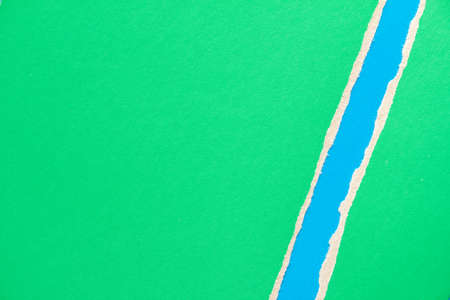 Green torn sheet of cardboard paper with blue stripe texture background. Stock fotó