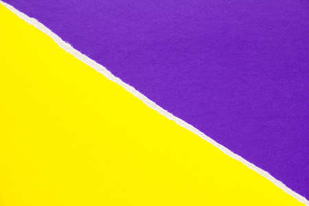 Yellow and purple torn sheet of cardboard paper with diagonal border texture background. Can be used for text.