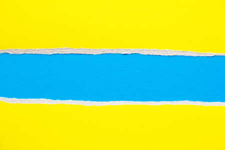 Blue and yellow torn and ripped sheet of cardboard paper texture background. Can be used for text.