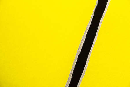 Yellow torn sheet of cardboard paper with black stripe texture background. Can be used for text.