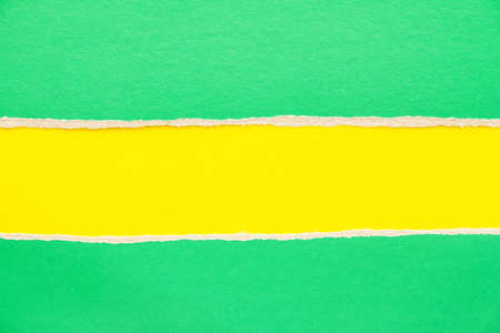 Green torn sheet of cardboard on yellow paper background. Can be used for text.