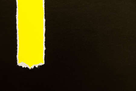 Black torn cardboard paper with yellow vertical stripe texture background. Can be used for text.