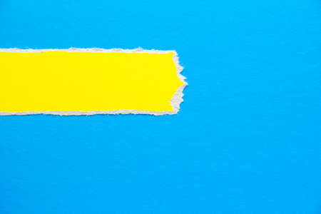 Blue cardboard paper with torn yellow horizontal stripe texture background. Can be used for text.