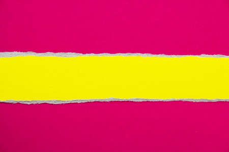 Torn yellow stripe of cardboard on scarlet red paper texture background. Can be used for text message.