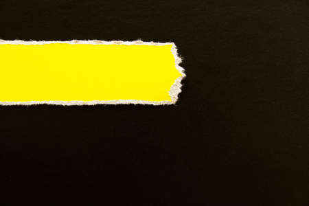 Black torn cardboard paper with yellow horizontal stripe texture background. Can be used for text.