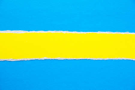 Closeuptorn stripe of yellow cardboard on blue paper texture background. Can be used for text.