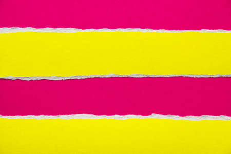 Scarlet red sheet of cardboard with yellow torn horizontal paper stripes. Can be used for text.
