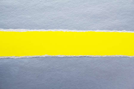 Torn stripe of yellow cardboard on silver gray paper texture background. Can be used for text. Stock fotó