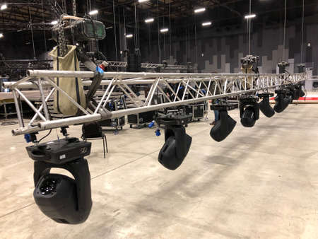 Installation of professional sound, light, video and stage equipment for a concert. Stage lighting equipment is clamped on a truss for lifting. Archivio Fotografico