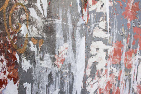 Old dirty urban wall with torn paper posters and peeling paint texture background.