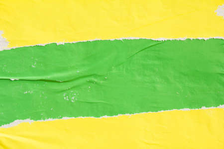 Green and yellow torn crumpled and peeling paper placards on urban billboard texture background. Copy space for text message. Stock fotó