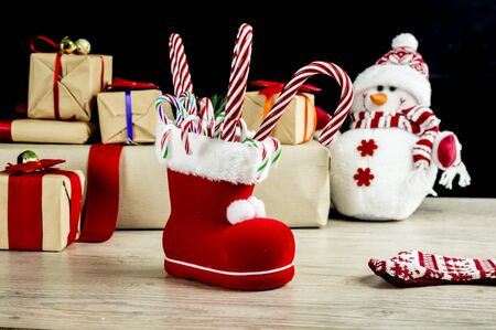 fill in: Christmas boot fill with candy canes, with snowman and presents in the background