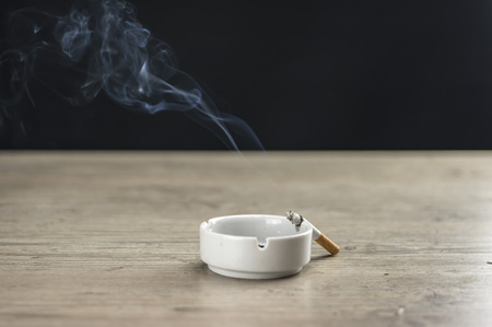 Lit cigarette burning in ashtray close up Stock Photo
