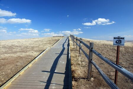 Path leading to lookout area in the badlands with a warning sigh