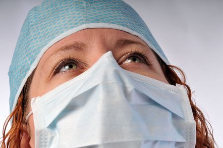a redheaded lady medical worker in a hat and mask