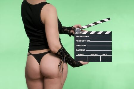 thongs: sexy young woman holding a movie clapper against a green screen