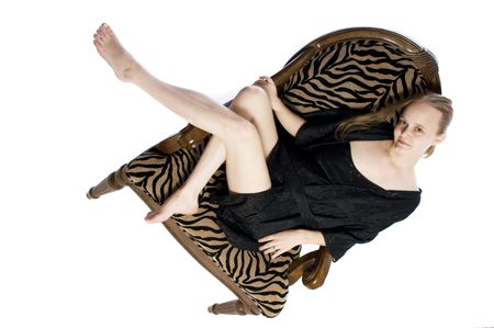 attractive young model in a zebra pattern chair on white background