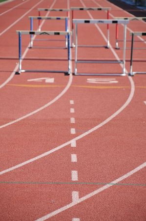 hurdles on a runners track with running lanes