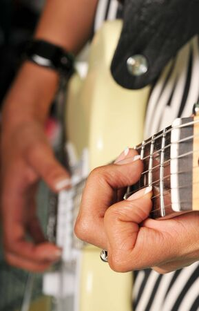 woman plays an electric guitar, images is selective focus on the neck hand