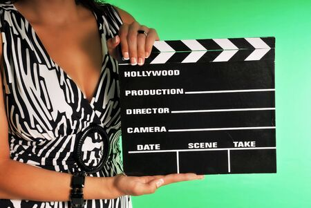 woman holding a movie clapper set against a chroma green screen