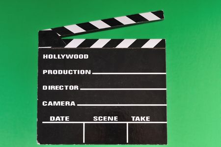 a movie marker or clapper board set against a green screen