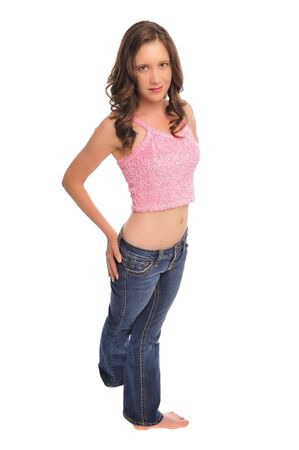 an attractive young woman in a pink top and jeans on a white background Stock Photo - 5463321