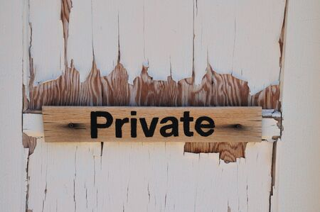 door casing: a sign on a door marked private with old paint  chipping off.