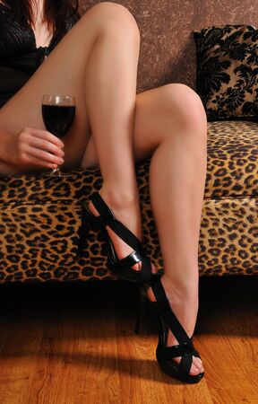 womans sexy legs and hand holding a glass of wine