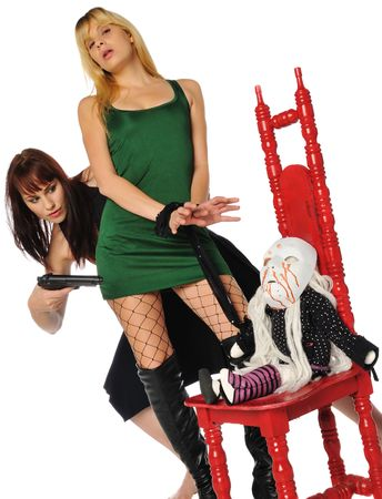 red head with a gun and a blonde tied to an evil little doll in a red chair Stock Photo