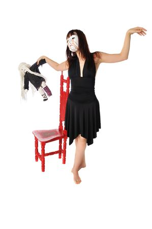 a woman in a mask dancing with a little doll on a white background photo