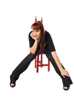 sit: attractive young redhead sitting in a chair on a white background Stock Photo