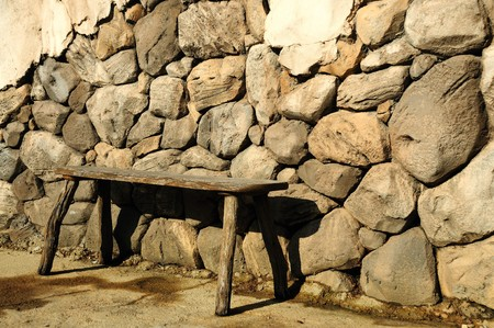 old wood bench up against a rock wall Banco de Imagens