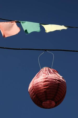 paper lantern hangs from a wire against a blue sky