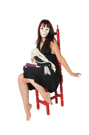 crazy woman in a mask playing with a doll on a white background