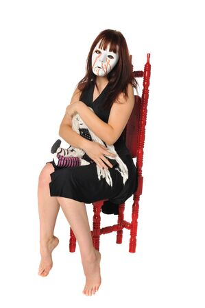 woman in a mask with a doll posing on a white background