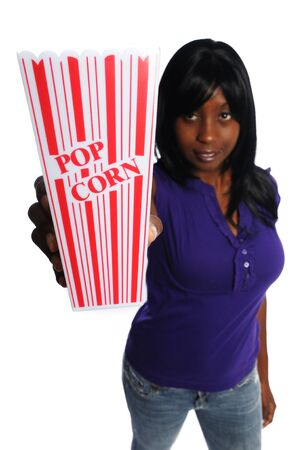 attractive african-american woman holding a container of popcorn on a white background