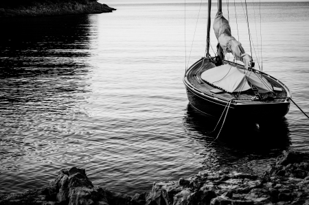 Sailing boat moored with a Landline to shore in BW photo