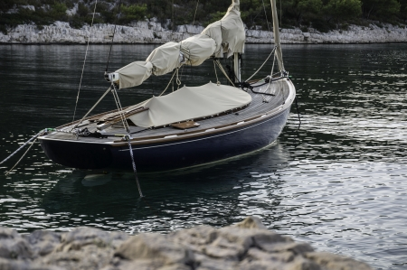 landlines: sailing boat is moored italian style with anchor and landlines to the shore Stock Photo