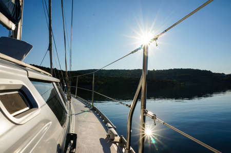 anchoring: sailing boat anchoring in calm water  sun is reflecting in the water  picture taken in croatia, adriatic sea Stock Photo